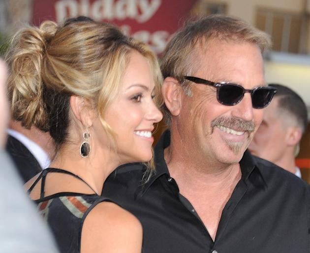 Actor Kevin Costner (R) and his wife Christine Baumgartner attend the premiere of Summit Entertainment's 'Draft Day', at the Regency Bruin Theatre in Los Angeles, California, on April 7, 2