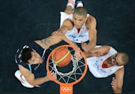 Argentinian guard Carlos Delfino (L) vies with French forward Nicolas Batum and French guard Tony Parker (R) during the Men's preliminary round group A basketball match of the London 2012 Olympic Games France vs Argentina at the basketball arena in London. France won 71 to 64