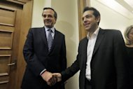 Alexis Tsipras, leader of the Coalition of the Radical Left party, SYRIZA, (R) shakes hands with Antonis Samaras, leader of the Conservative 'New Democracy' party, before their meeting at the Greek Parliament in Athens