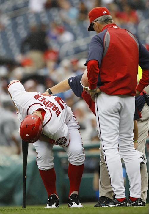 Washington Nationals Bryce Harper reacts to being hit by a foul tip as manager Davey Johnson and a trainer stand by during the first inning of the first baseball game of a doubleheader against the Atl