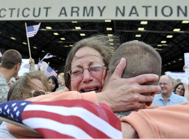 ** FOR USE AS DESIRED, YEAR END PHOTOS ** FILE -In this Aug. 25, 2010 file photo, Janet Allegra, of Ellington, hugs her son Spc. John Allegra IV at the Army aviation support facility in Windsor Locks,