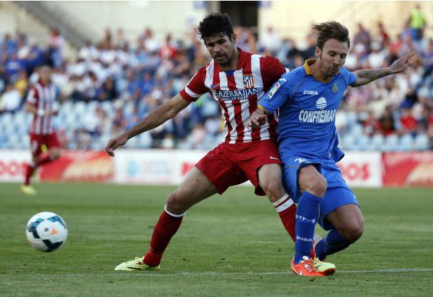 Atletico Madrid's Costa is challenged by Getafe's Delgado during their Spanish first division soccer match in Getafe