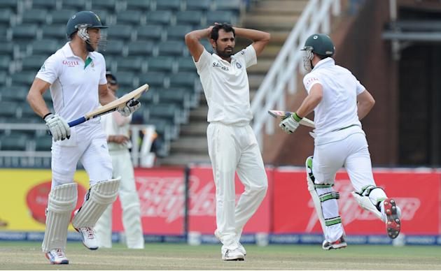 South African batsman Faf du Plessis and AB de Villiers run between the wickets as Indian bowler Mohammed Shami (C) reacts on the 5th day of a first cricket Test match between South Africa and India i