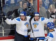 Finnish players celebrate scoring against team USA during a quarter-final game of the IIHF International Ice Hockey World Championship in Helsinki