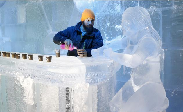Sculptor Bouchard of Canada poses near a sculpture at the ice bar of the Brussels Ice Magic Festival