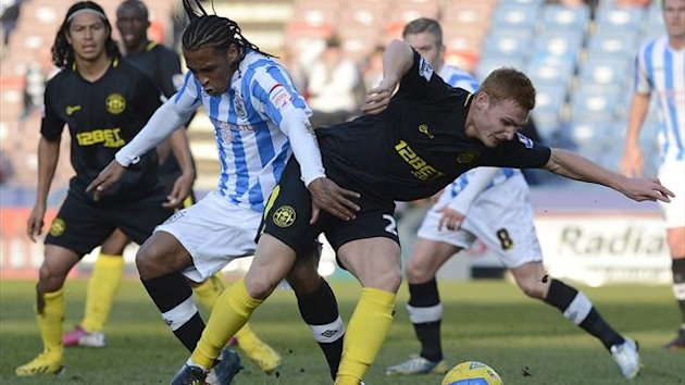 Wigan Athletic's Fraser Fyvie (R) challenges Huddersfield Town's Neil Danns during their English FA Cup match
