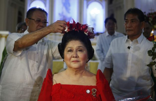 A supporter crowns former Philippine first lady Imelda Marcos with flowers during a traditional birthday ritual as she celebrates her 85th birthday in Batac