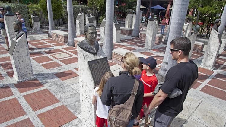 In this Wednesday, March 13, 2013, photo provided by the Florida Keys News Bureau, Kate and Matt Hover, and their three children examine a bronze bust of former President Harry S. Truman in the Key West Historic Memorial Sculpture Garden in Key West, Fla. The free-admission gardens features 38 bronze busts of prominent men and women who had a key influence on the development of Key West and the remainder of the Florida Keys.  (AP Photo/Florida Keys News Bureau, Carol Tedesco)