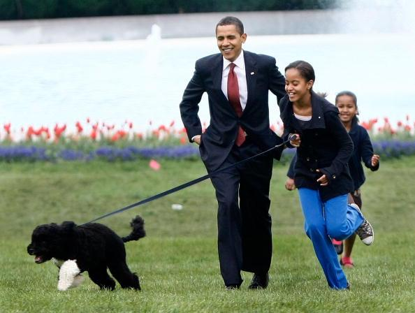 U.S. President Barack Obama with his daughters Malia (C) and Sasha (R) walk the family's new Portuguese water dog Bo, during the dog's introduction to the White House press corps on the South Lawn of