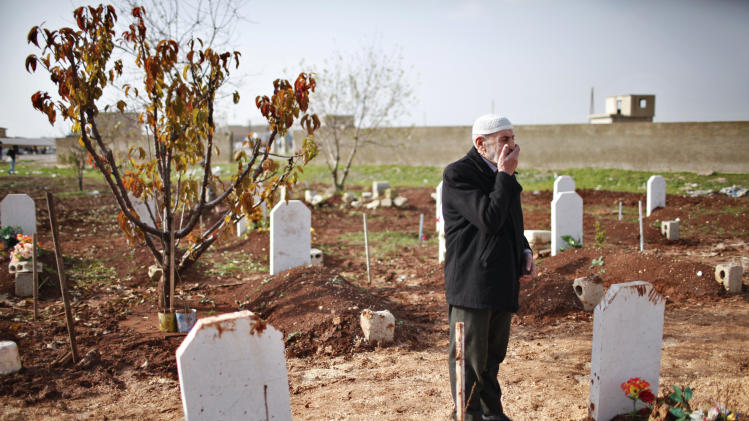 Abdlhamid Haj Omar, 70, a father who lost three sons and two grandsons in the ongoing Syrian crisis, reacts as he visits their graves at the Martyrs' cemetery in Azaz city, North Aleppo