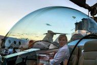 A woman sits in a helicopter cockpit -- made with a polycarbonate material -- during the annual LABACE (Latin American Business Aviation Conference and Exhibition) at Congonhas Airport, in Sao Paulo, Brazil on August 16. The air show this week turned the spotlight on the robust health of Brazil's general aviation market, which is thriving despite the global economic slowdown