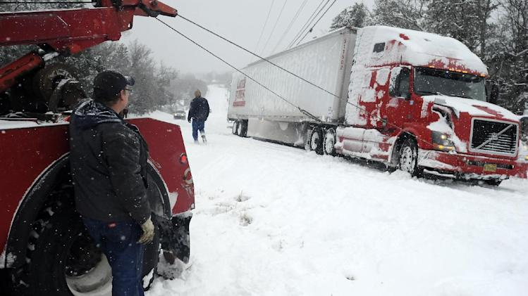 Jim Dobbs, left, helps pull a tractor trailer rig out of a ditch Friday, Dec. 6, 2013, in Henderson, Ark. The icy storm plowing across the country is delaying shipments of everything from Christmas presents to cooking grease. (AP Photo/The Baxter Bulletin, Kevin Pieper) NO SALES