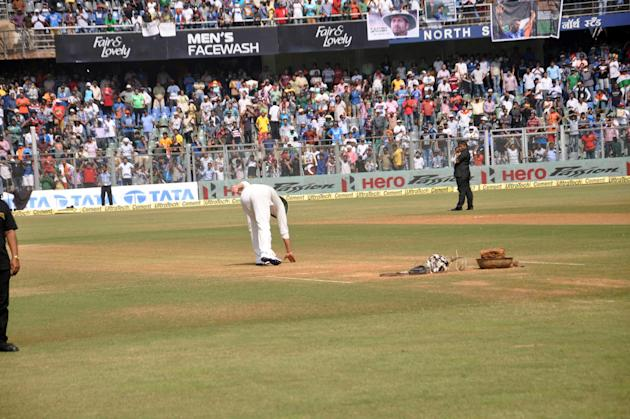 Cricket legend Sachin Tendulkar touches the pitch as he bids adieu to international cricket in Mumbai on Nov.16, 2013. (Photo: Sandeep Mahankal/IANS)