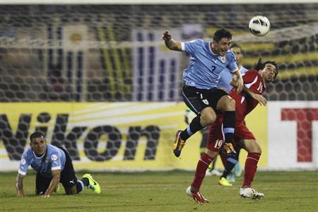 Cristian Rodriguez of Uruguay fights for the ball with Alaa Al-Shaqran of Jordan during their World Cup qualifying playoff first leg soccer match at Amman International stadium
