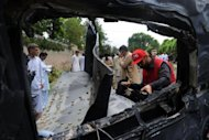 Pakistani rescuers inspect the badly damaged US consulate vehicle at a bomb blast site in Peshawar. A suicide car bomber rammed a US consulate vehicle in Pakistan on Monday, killing at least two people in the deadliest attack targeting Americans in the country in more than two years