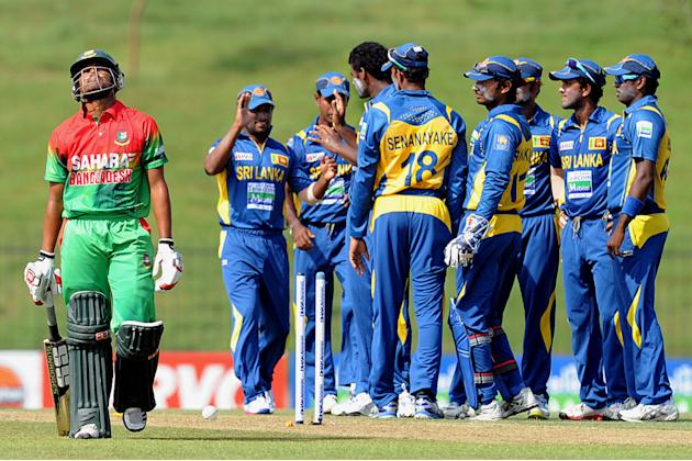 Bangladeshi cricketer Anamul Haque (L) leaves the field as Sri Lankan cricketer Thisara Perera (4L) celebrates with teammates during the opening one-day international (ODI) match between Sri Lanka and