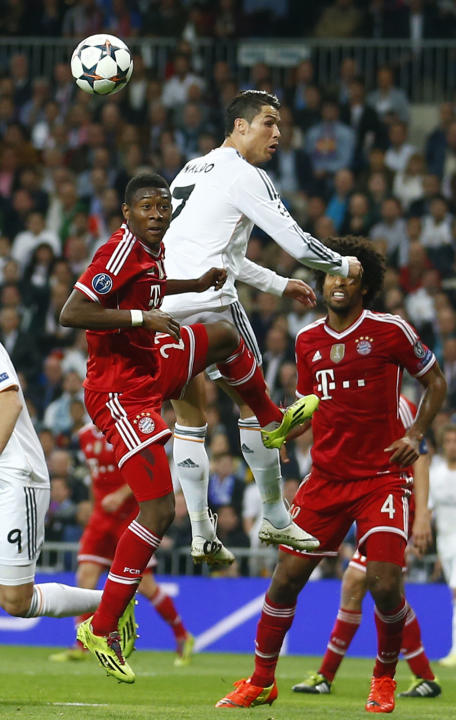 Real's Cristiano Ronaldo, center, and Bayern's David Alaba, left, go for a header during a  Champions League semifinal first leg soccer match between Real Madrid and Bayern Munich at the Santi