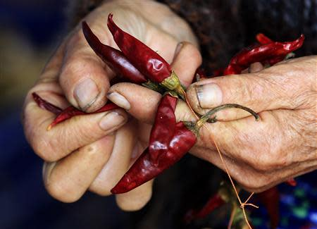 A close up shows drying peppers being cleaned, near Batya