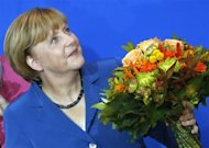 German Chancellor and leader of the Christian Democratic Union (CDU) Angela Merkel smiles as she receives flowers after first exit polls in the German general election (Bundestagswahl) at the party headquarters in Berlin September 22, 2013. REUTERS/Wolfgang Rattay