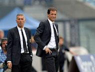 AC Milan's coach Massimiliano Allegri (R) grimaces next to his assistant Mauro Tassotti during the last minute of the Serie A football match against Udinese at Friuli stadium in Udine. Udinese won 2-1
