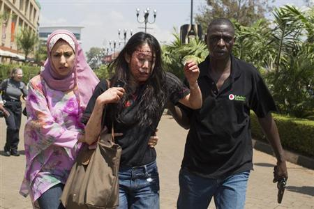 An injured woman (C) is helped out of the Westgate Shopping Centre where gunmen went on a shooting spree, in Nairobi September 21, 2013. REUTERS/Siegfried Modola