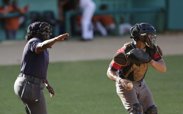 Cuban umpire Yanet Moreno (L) calls a Camaguey player out on strikes as Villa Clara's catcher holds a ball during a baseball game in Villa Clara October 18, 2014. At 39, she is the only woman in the world umpiring top-flight professional baseball. She is in her 11th season in the National Series, Cuba's premier baseball league, and says she is ready for the international stage. Cuba has yet to offer Moreno one of its umpiring spots in a top international event for men. Picture taken October 18, 2014. REUTERS/Enrique De La Osa (CUBA - Tags: SPORT BASEBALL)