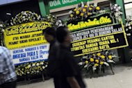 Floral condolence message boards line up the arrival entrance of Halim Perdanakusuma airport in Jakarta, on May 12, as bodies of the Sukhoi plane crash victims arrive in the Indonesian capital for identification