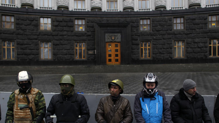 Protesters guard the Ukrainian government building in Kiev, Ukraine, Sunday, Feb. 23, 2014. The Kiev protest camp at the center of the anti-President Viktor Yanukovych movement filled with more and more dedicated demonstrators Sunday morning setting up new tents after a day that saw a stunning reversal of fortune in a political standoff that has left scores dead and worried the United States, Europe and Russia. (AP Photo/ Marko Drobnjakovic)