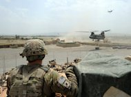 A US soldier keeps guard as US military Chinook helicopters unload fuel supplies at a base in Afghanistan. A new defense bill passed by US lawmakers would provide $518 billion for the Pentagon and an additional $88.5 billion for overseas contingency operations, specifically the war in Afghanistan and counterterrorism efforts, for the fiscal year that begins October 1.