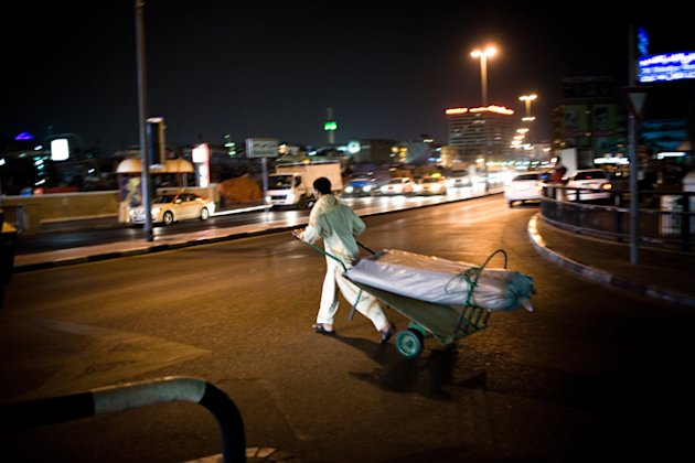 A migrant worker carts rugs down a dark city street in Dubai.