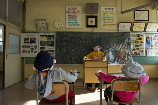 Scarecrows representing pupils and a teacher sit in a classroom in a closed down school. (Reuters)