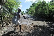 A child walks through damaged fields in Leogane, south of Port-au-Prince, one day after hurricane Sandy passed through Haiti on October 27. Sandy's tear across the Caribbean left 51 people dead in Haiti, while another 15 people were still missing after the deadly storm, officials said Sunday