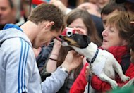 A dog licks British tennis player Andy Murray (L) as he meets with fans in the centre of Dunblane, Scotland, following his victory in the US Open tennis tournament and gold medal in the London 2012 Olympic Games
