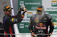 Red Bull Formula One driver Mark Webber (R) of Australia is sprayed with champagne by teammate Sebastian Vettel of Germany and Ferrari Formula One driver Fernando Alonso of Spain (unseen) during podium celebrations after the Brazilian F1 Grand Prix at the Interlagos circuit in Sao Paulo November 24, 2013.