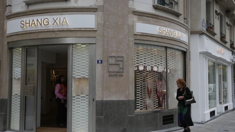 A woman walks past the shop of the young brand Shang Xia on its opening day in Paris