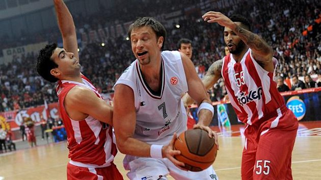 Siena's David Andersen (C) Olympiakos Piraeus' Kostas Sloukas during their Euroleague basketball game in Athens