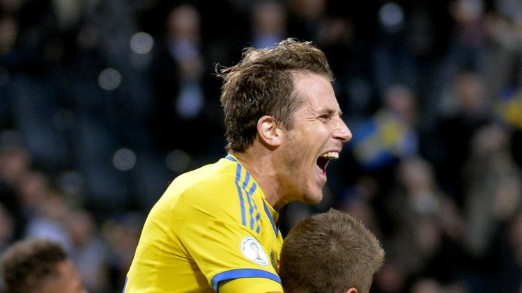 Sweden's Alexander Kacaniklic, bottom, celebrates with teammate Tobias Hysen, left, after scoring his team's second goal during the 2014 World Cup group C qualifying soccer match between Sweden and Germany at Friends Arena in Stockholm, Sweden, on Tuesday Oct. 15, 2013