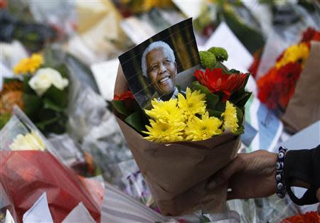 Flowers and tributes are left for South Africa's former president Nelson Mandela at South Africa's High Commission in London