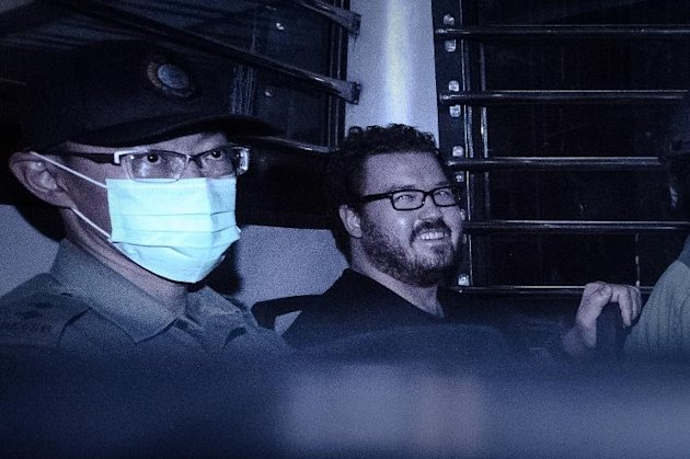 British banker Rurik Jutting, charged with the grisly murders of two women, smiles as he sits in a prison van leaving court in Hong Kong on November 10, 2014