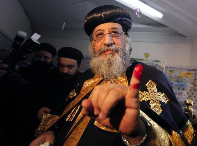 Pope Tawadros II, pope of the Coptic Orthodox church, shows off his finger as he casts his vote in a referendum at a polling station in Cairo