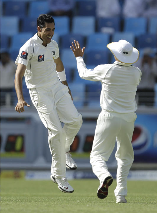 Pakistan's Umar Gul, left, celebrates taking the wicket of England's Alastair Cook, not pictured, during the first day of the third cricket test match of a three match series between England and Pakis