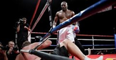 Evander Holyfield of the U.S. stands over Francois Botha of South Africa after knocking down Botha in the eighth round of their heavyweight bout at th...