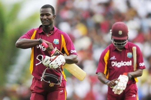 West Indies captain Darren Sammy (L) and teammate Kemar Roach leave the field after being run out