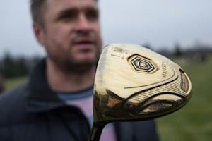 A man holds a golf club with the name of Ukrainian …