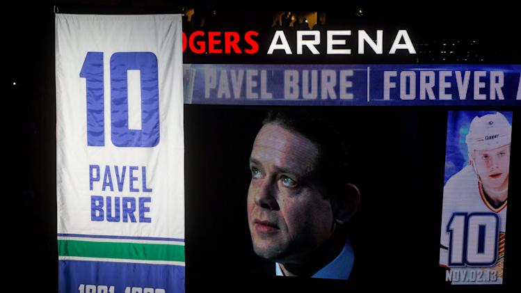 Retired Vancouver Canucks forward Pavel Bure, of Russia, is displayed on a video screen as he watches his number 10 retired and lifted to the rafters during a ceremony before the Canucks NHL hockey game against the Toronto Maple Leafs in Vancouver, British Columbia, on Saturday Nov. 2, 2013