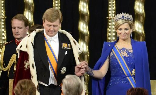 King Willem-Alexander of the Netherlands (L) holds the hand of his wife Queen Maxima during his inauguration at the Nieuwe Kerk (New Church) in Amsterdam on April 30, 2013. AFP PHOTO / POOL / LEX VAN