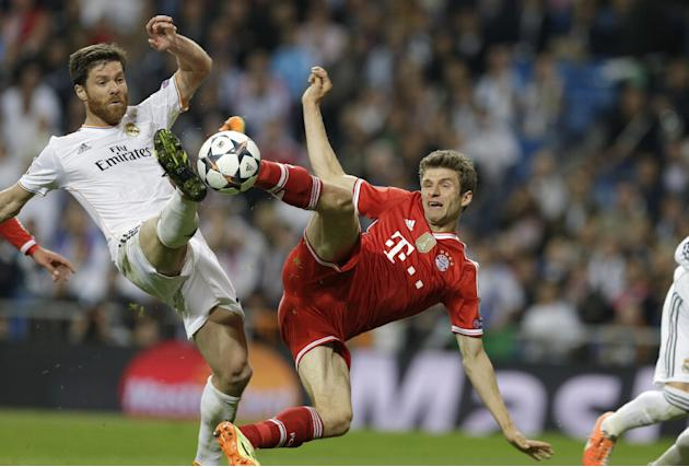 Real's Xabi Alonso, left, and Bayern's Thomas Mueller challenge for the ball during a  Champions League semifinal first leg soccer match between Real Madrid and Bayern Munich at the Santiago B