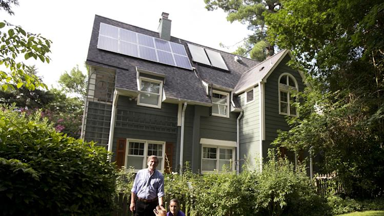 "In this Thursday, July 18, 2013 photo, Ketch Ryan, right, and her neighbor Kirk Renaud, pose next her house with solar panels on the roof in Chevy Chase, Md. ""In many ways we found that a lot of people were afraid to go solar because they were too afraid of what they didn't know,"" said Ryan, who had a solar energy system installed in her house several years ago. To assist neighbors, Ryan helped establish a cooperative, Common Cents Solar, co-founded with Renaud, ""to make sure we didn't have to reinvent the wheel. We can do it together and we can do it more efficiently,"" she said. (AP Photo/Manuel Balce Ceneta)"