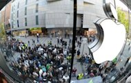 Customers queue to enter the Apple Store in the southern German city of Munich