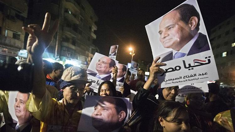 Egyptian supporters of former army chief Abdel Fattah al-Sisi hold portraits of him as they watch him on a screen in downtown Cairo on May 5, 2014